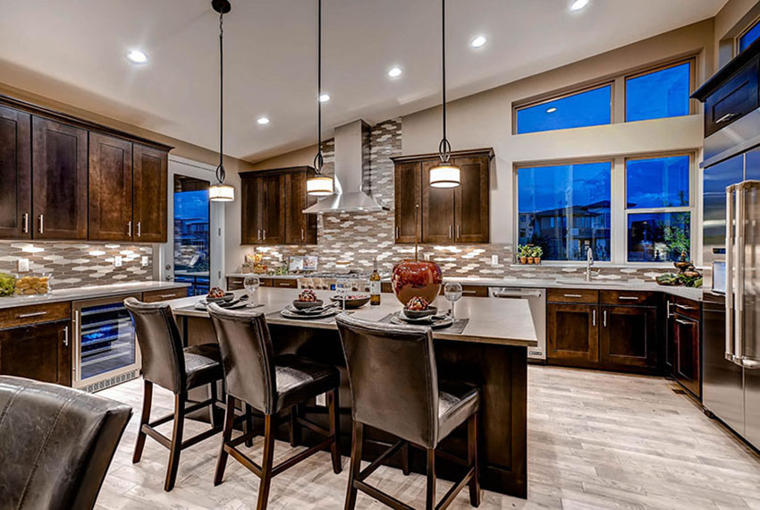 A beautiful, modern kitchen, designed by Godden Sudik Architects, with an oversized island, and high-end kitchen appliances.
