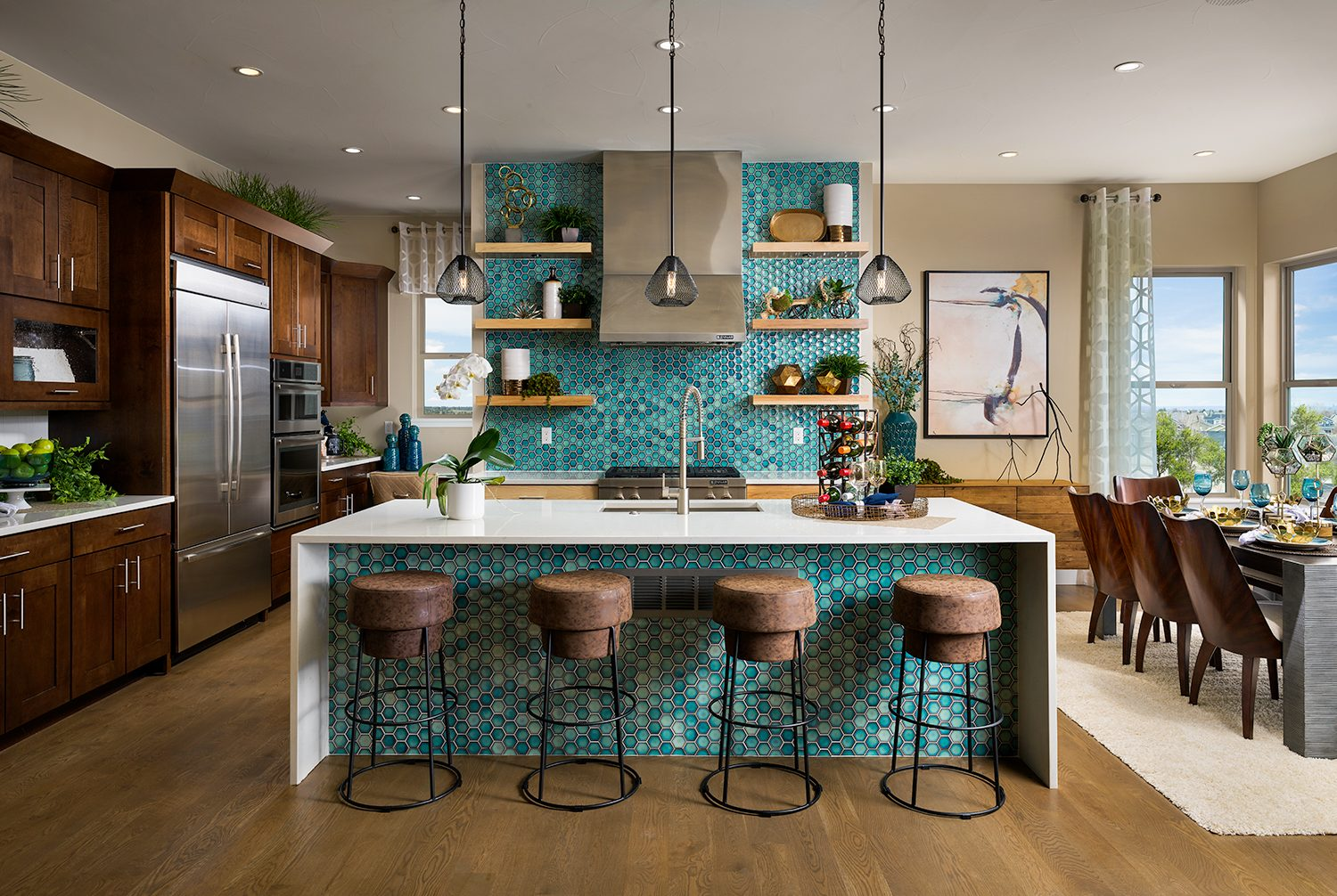 Gorgeous modern kitchen with vibrant turquoise accent backsplash and island designed by Godden Sudik Architects