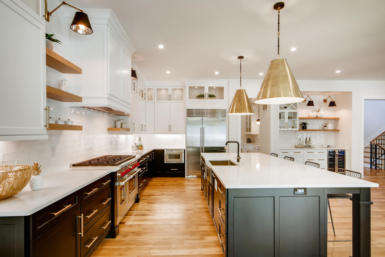 An updated take on the modern farmhouse kitchen with open shelving, a large center island, and contrasting cabinets