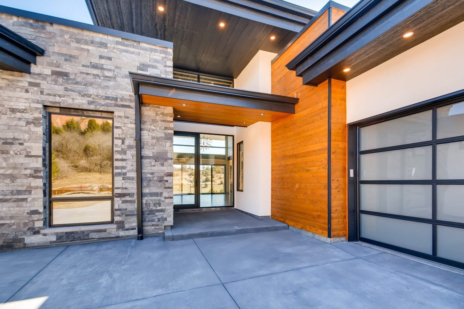 Modern home front entry designed by Godden Sudik Architects that features cantilevered flat roof and wood accents