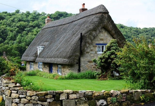 straw roof and stone english cottage