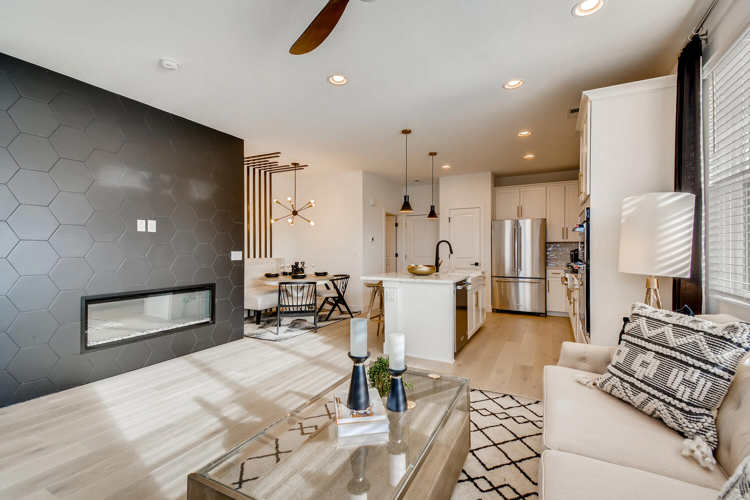 Open concept floor plan of modern townhome by residential architect in colorado featuring linear fireplace and accent wall